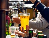 Bartendern häller öl i plast- exponeringsglas under gatamatfestival Arkivbild