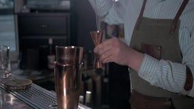 Bartendern häller alkoholdrycken in i den lilla shaker arkivfilmer