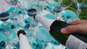 Bartendern häller champagne in i exponeringsglas från pyramiden stock video