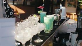 Bartendern häller isen in i exponeringsglaset och häller turkoscoctailen stock video