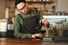 Bartendern häller kaffe i ett exponeringsglas Arkivbild