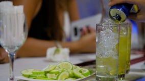 Bartendern häller kolsyrat vatten i ett exponeringsglas med is