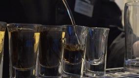 Bartendern häller många B52 eller whisky Bartender som häller den nya coctailen i utsmyckat exponeringsglas Bartendershow _ royaltyfri bild
