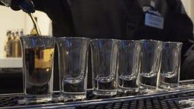 Bartendern häller många B52 eller whisky Bartender som häller den nya coctailen i utsmyckat exponeringsglas Bartendershow _ royaltyfria foton