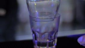 Bartendern med två exponeringsglas gör en coctail i nattklubben arkivfilmer