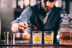 Bartendern räcker att förbereda den gammalmodiga whiskycoctailen på stångräknare royaltyfri fotografi