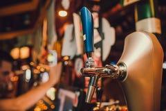Bartendern räcker att hälla ett lageröl i ett exponeringsglas arkivbilder