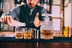 bartendern räcker att tillfoga is och whisky till moderna stads- coctailar Himmelstång som tjänar som eleganta drinkar royaltyfri foto