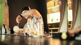 Bartendern rör isen i den glass långa skeden stock video