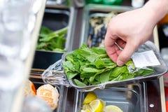Bartendern river sönder sidor av mintkaramellen för fruktcoctailar Stångräknare Bartendern på stången förbereder uppfriskande fru royaltyfri bild
