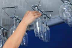 Bartenderns hand ger tomma exponeringsglas från stångshelen royaltyfri fotografi