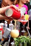 Bartenders hand med den hällande coctailen för skakablandare in i exponeringsglas royaltyfri foto