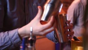 Bartendrar med den hällande coctailen för shaker in i exponeringsglas 2 lager videofilmer