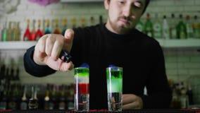 Bartendrar visar, grabben med tändaren i armuppsättning på brandcoctailen med färglager i tunt exponeringsglas på stångräknare lager videofilmer