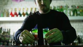 Bartendrar visar, män med tändaren i handuppsättning på brandalkoholdrycken med färglager i tunt exponeringsglas på stångtabellen stock video