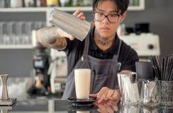 Bartista derrama o cocktail do leite no vidro dentro do restaurante do estilo do projeto moderno com contador da barra Foto de Stock