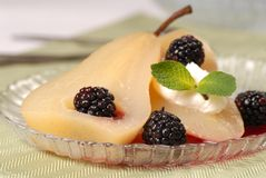 Bartlett pear poached in wine with blackberries Royalty Free Stock Photos