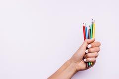 Barwiący ołówki w żeńskiej ręce z manicure'em na menchii Fotografia Stock