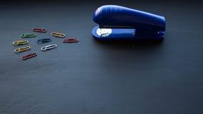 Barwić klamerki na czarnym tle i zszywacz zdjęcia stock