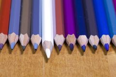 Barwi ołówki z rzędu, jeden ołówkowy stawiający naprzód mała głębia ciętość zdjęcia stock