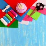 Barwiona filc ciąć na arkusze, szwalny zestaw, nożyce, szpilki, pincushion, biały faborek na błękitnym drewnianym tle z pustą prz Fotografia Stock