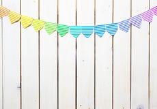 Barwiona flaga girlanda Tło jest białym drewnem Zdjęcie Stock