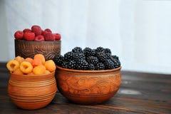 Barwione jagody czerwień, malinki lub czernicy w earthenware na stole, żółte i czarne obraz royalty free