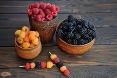 Barwione jagody czerwień, malinki lub czernicy w earthenware na stole, żółte i czarne zdjęcie royalty free