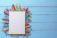 Barwione kredki, papierowe klamerki, szpilki i otwarty notatnik, zdjęcia royalty free