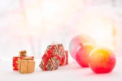 Barwione piłek i bożych narodzeń teraźniejszość na śniegu abstrakcjonistycznych gwiazdkę tła dekoracji projektu ciemnej czerwieni Fotografia Royalty Free