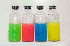 Barwione substancje chemiczne, szklane butelki na białym tle Zdjęcia Royalty Free