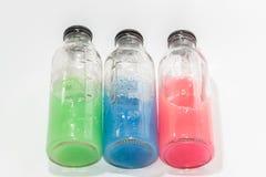 Barwione substancje chemiczne, szklane butelki na białym tle Zdjęcia Stock