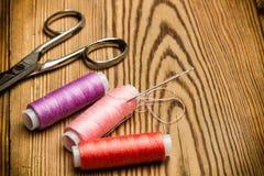 Barwione szwalne nici i nożyce zdjęcia stock