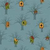 Barwioni birdhouses z drzewami na błękitnym tle Obraz Stock