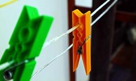 Barwioni clothespins wiesza od nici Zdjęcia Stock