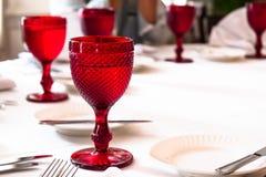 Barwioni czerwoni matte szkła na stole Zamazani ludzie na tle Obrazy Stock