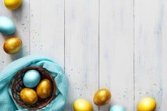 Barwioni Easter jajka w małym koszu na drewnianym tle Zdjęcie Royalty Free