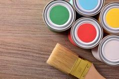 Barwioni farba garnki, muśnięcie na drewnianym stołowym odgórnym widoku i zdjęcia stock
