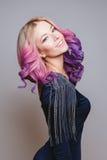 Barwioni hairs Portret uśmiechnięte kobiety z barwionymi kędzierzawymi hairs w sukni na popielatym tle zdjęcia royalty free