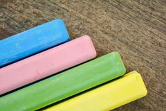 Barwioni kredowi kije na starej drewno desce jako kopia interliniują tło obraz stock