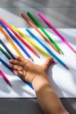 Barwioni ołówki i dziecko ręka na stole Obrazy Stock
