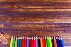 Barwioni ołówki kłama z rzędu na drewnianej powierzchni zdjęcie stock