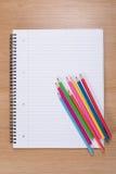 Barwioni ołówki przeciw puste miejsce spirali segregatorowi zdjęcie royalty free