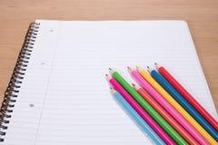 Barwioni ołówki przeciw pustemu notatnikowi zdjęcie stock