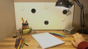 Barwioni ołówki są na stole Obsługuje ` s rękę bierze ołówek i chce rysować na powierzchni 4k zbiory wideo