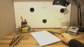 Barwioni ołówki są na stole Obsługuje ` s rękę bierze ołówek i chce rysować na powierzchni 4k zdjęcie wideo