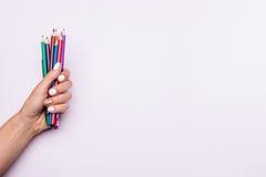 Barwioni ołówki w żeńskiej ręce z białym manicure'em na świetle Fotografia Stock