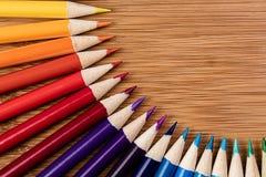 Barwioni ołówki w kurenda wzorze na bambusa stole A obraz stock