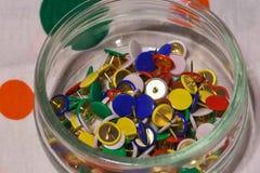 Barwioni thumbtacks w szklanym słoju zdjęcia stock