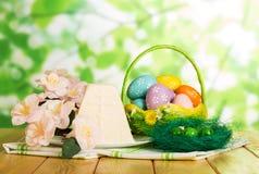 Barwioni Wielkanocni jajka w koszu, na gniazdeczku, Wielkanocny cheesecake desser obrazy royalty free